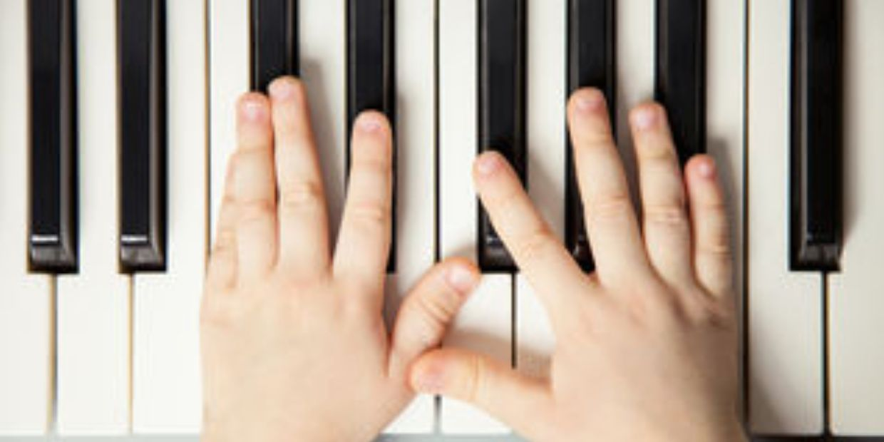 young child's hands on piano keys