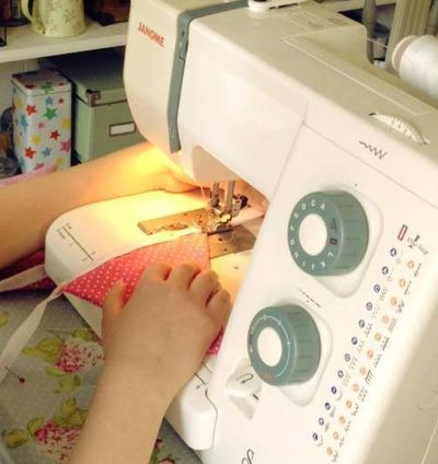 someone using a sewing machine to make some bunting