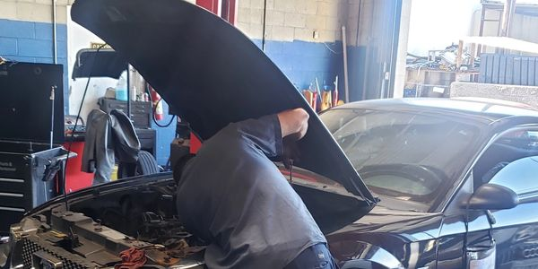 Mechanic Working on a Ford Mustang in he bay with a lift hoist.