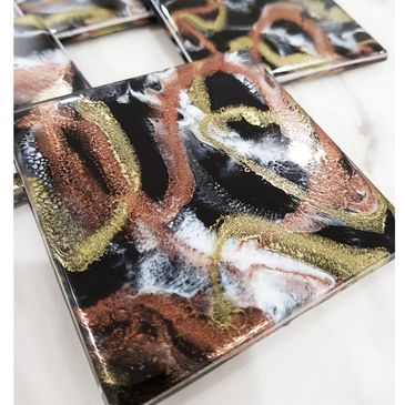 set of 4 coasters. colours are black gold copper and white.