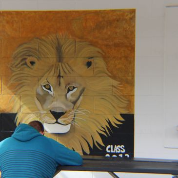 An apprentice  looking at the IUPAT lion painted on while wall outside.