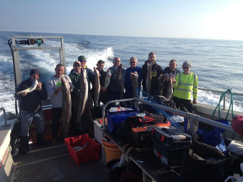 10 anglers standing at the back of seawatch boat fishing from Mylor harbour Falmouth Cornwall