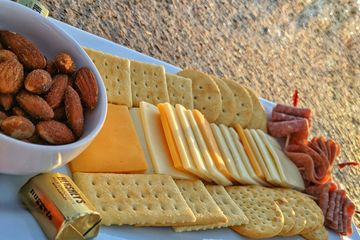 Snack plate - nuts, crackers, cheese, salami, chocolate - on granite table