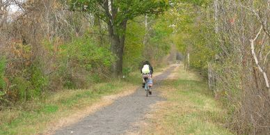 A person riding  their bike along the D&H Rail trail gravel path.