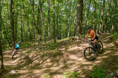 A young adult and woman mountain bike around a singletrack corner.