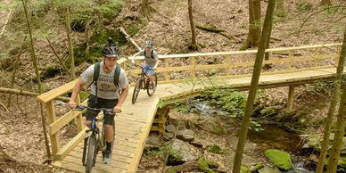 Two young men mountain bike over a bridge with railing above a stream.