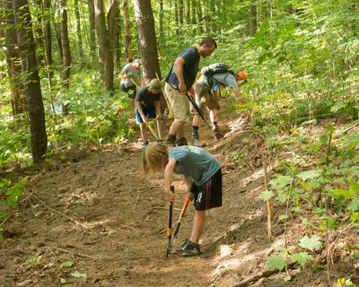 two kids and three adults use hand tools to clip roots on a new trail in the woods.