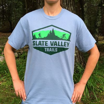 Person standing in shirt with hands on hips. Slate Valley Trails logo is on center of grey shirt.