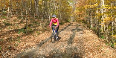 Middletown Springs - a person biking on an old gravel road covered with leaves