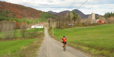 A cyclist bikes toward a farm on a backroad on a fall day.