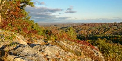 A fall scene from Mt Zion of mountains and trees from a rocky outcropping