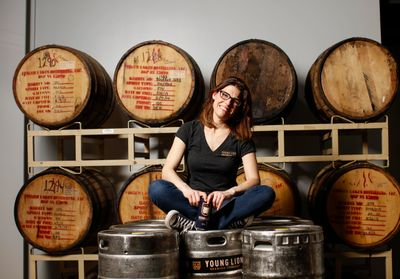 CEO Jen Newman in the brewhouse sitting on kegs in front of beer aging in bourbon barrels.