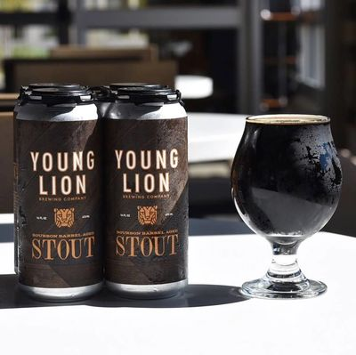 4 pack of Young Lion Bourbon Barrel Stout next to a glass of stout.