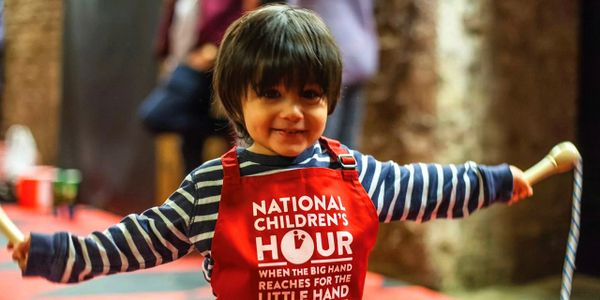 Child wearing National Children's Hour bib skipping