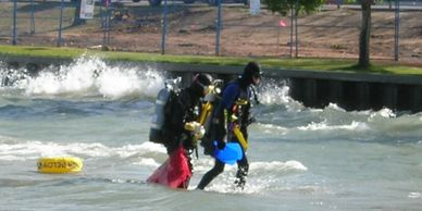 Scuba Divers leaving rough water at Sylvan Lake, Alberta.