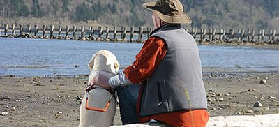 A PERSON IN FISHING GEAR SITTING DOWN OVER LOOKING A WATERS VIEW BY HIS GUIDE DOG.