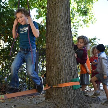 Santa Cruz Children's School students playing on a slackline during recess.