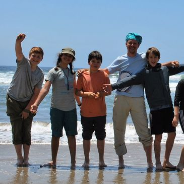 Santa Cruz Children's School students celebrating at the beach after their backpacking trip.