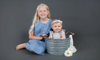 two smiling little girls wearing blue