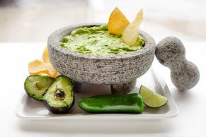 stone bowl full of guacamole and chips