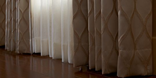 Draperies, quality and affordable window treatments, over a living room in Panama City Florida