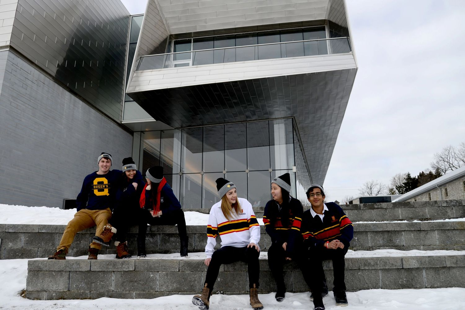 People wearing branded Queen's University clothing sit outside the Isabel in winter.