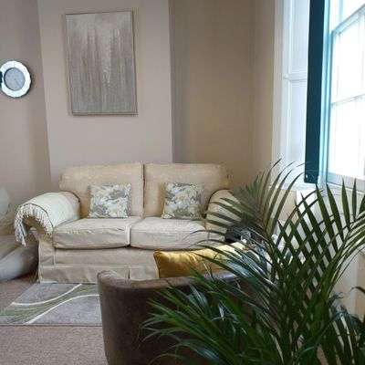 A warm and light counselling room with a sofa, bean bag tub chair and plants in.