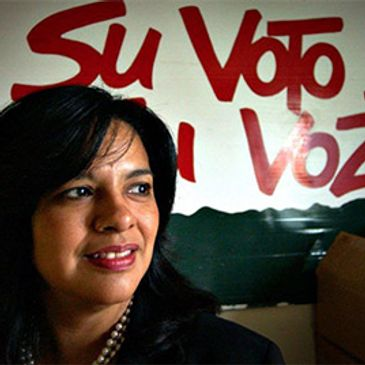 President of SVREP Lydia Camarillo in front of the organization's slogan, Su Voto Es Su Voz.