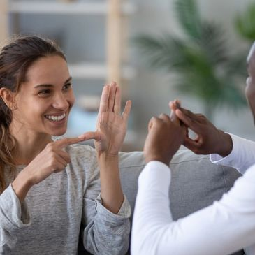 Smiling mixed ethnicity couple or interracial friends talking with sign finger hand language