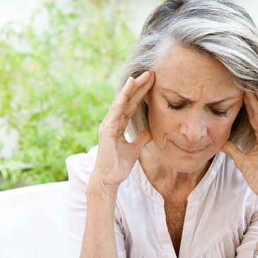 Mature woman touching her head with her hands while having a headache pain