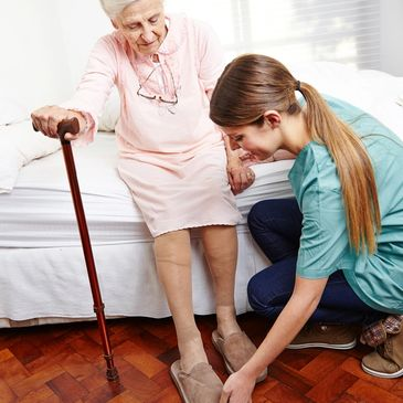 Caregiver helps dressing senior citizen woman