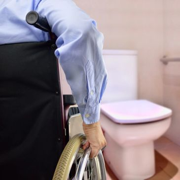 rear view of man on wheelchair going to the toilet adapted for disability person