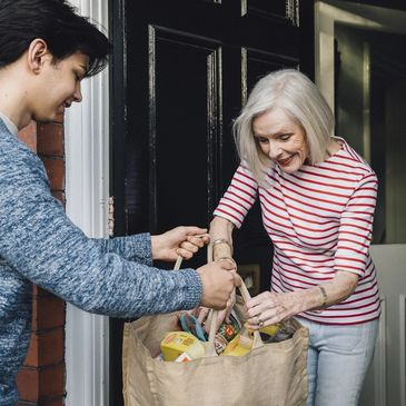 Teenage boy is delivering some groceries to an elderly woman