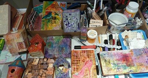 Colorful art on canvas and wood in varying stages of completion and some of the supplies Claire Bull