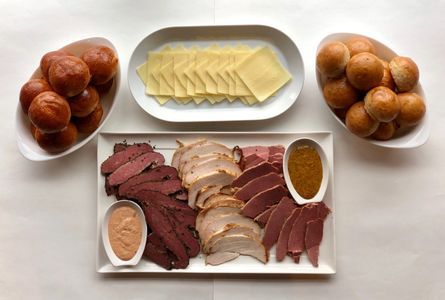 Image Description: Deli platter with three different kinds of meat, cheese, and housemade rolls.