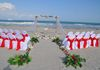 white silk and greenery aisle way with red accents.  Shown here with matching heart , chairs and sand unity table.