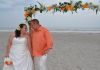 bamboo arch with white silks and orange accents.