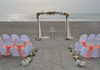 bamboo arch with white silk and orange accents.  Shown with covered chairs, aisle way and sand ceremony table.