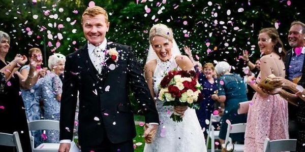 Confetti being thrown as happily married couple walk down the aisle.