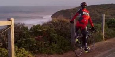 Road cyclist stopped along Great Ocean Road overlooking Bells Beach
