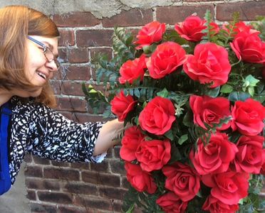 Lana working on a beautiful red-rose standing spray.