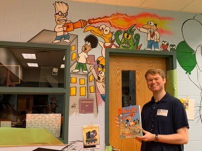 Author Michael Thompson holds his first Chicken Boy in front of a mural of his book's characters.