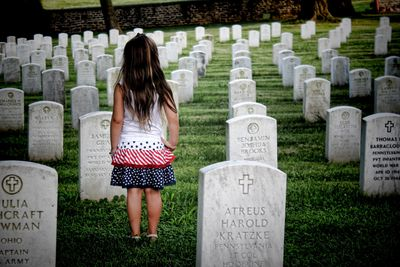 Photo of child walking amongst military grave headstones