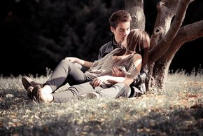 A young couple romantically reclining against a tree.