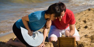 Two young adults finding a small treasure chest at the beach.