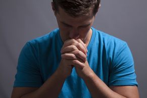A young man bowing his head in prayer.