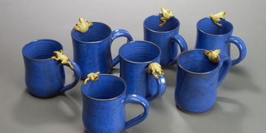 blue mugs with little green frogs on the rims