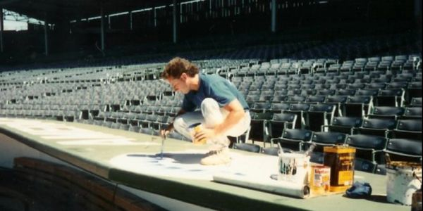 *Robert Ryan painting the All-Star logo on the National League Dugout at Wrigley Field in 1990.*