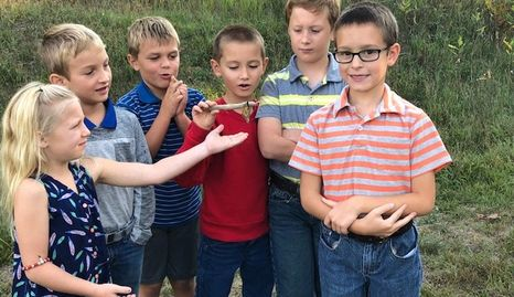 First Graders releasing a monarch butterfly that hatched in their classroom.