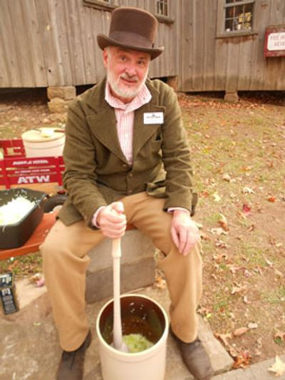 Pioneer man packing sliced cabbage in a crock to make sauerkraut.